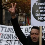 """A man holds a placard reading """"Don't touch my HDP (pro-Kurdish Peoples' Democratic Party) MP"""" and flashes a victory sign during a protest in Paris on November 5, 2016, following the arrest of the two co-leaders of Turkey's main pro-Kurdish party. An Istanbul court today ordered the imprisonment of nine staff from the opposition Cumhuriyet newspaper, in an intensifying crackdown a day after the leaders of the country's main pro-Kurdish party were also jailed. Nine MPs from the opposition pro-Kurdish People's Democratic Party (HDP), including its co-leaders Selahattin Demirtas and Figen Yuksekdag, were also jailed ahead of trial by the courts on November 4 on terror charges. / AFP PHOTO / GEOFFROY VAN DER HASSELT"""